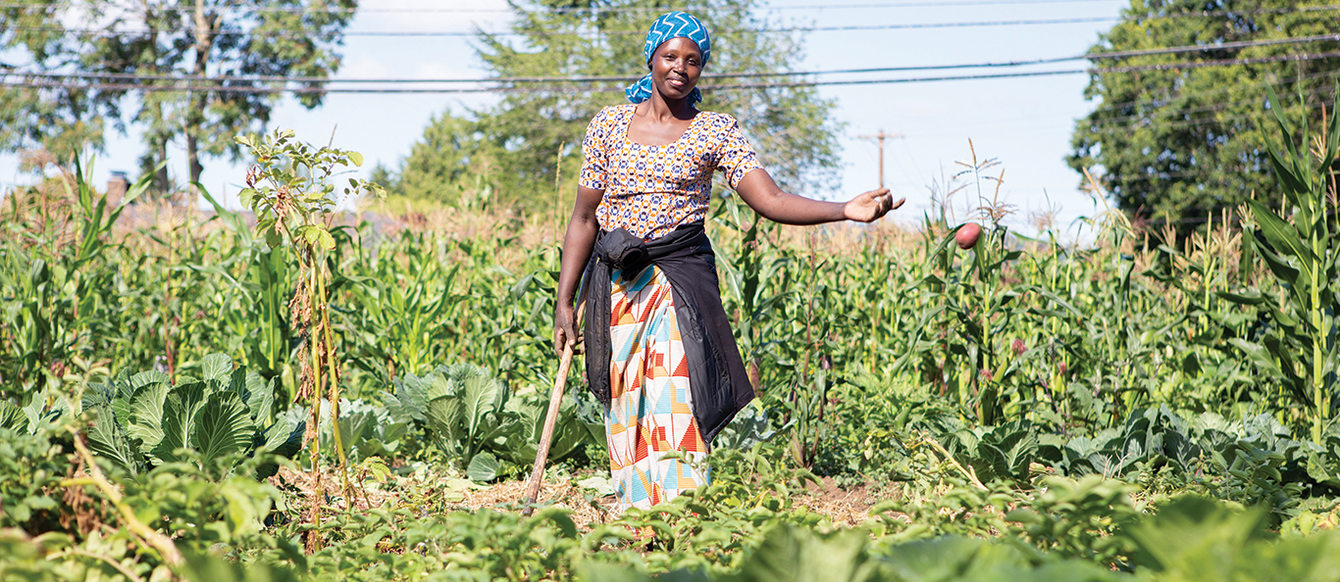 A black woman, standing in a garden and wearing a blue head wrap, smiles as she tosses a potato into a pile.
