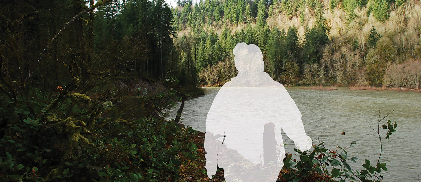 A silhouette of a person walks in a forest with a river in the background.