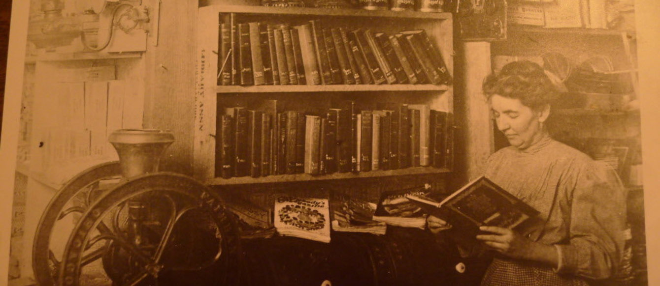A sepia-tone photograph of a woman reading a big, leather-bound book in front of a shelf of other big, leather-bound books.