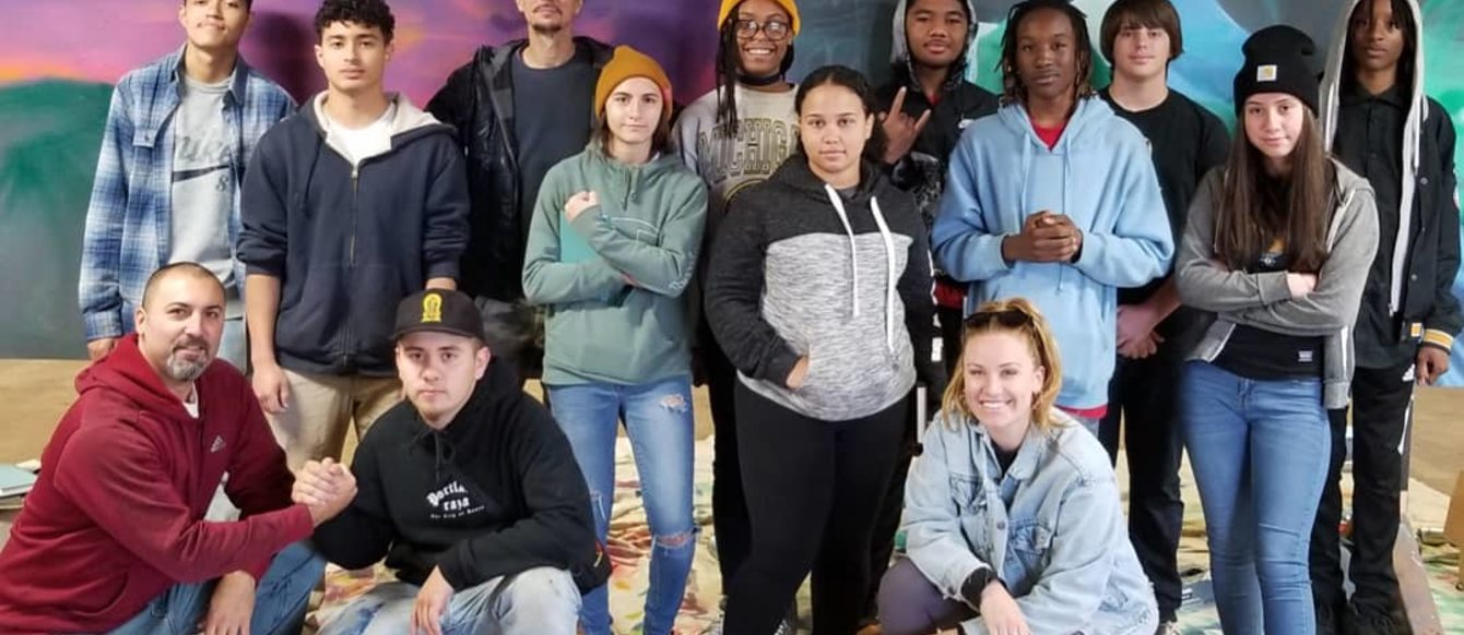 Young artists pose for a picture in front of a mural in progress