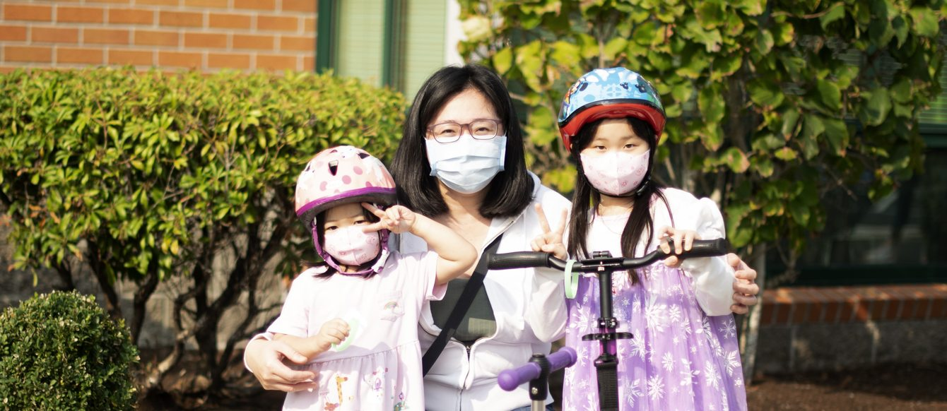 Mother and two children pose wearing masks and helmets