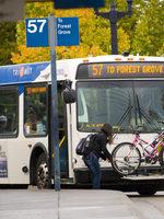 photo of woman loading a bike onto a bus