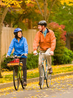 photo of man and woman biking through autumn leaves