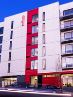 a photo of a stark white building with a large vertical red stripe