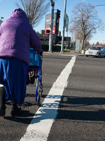 A woman pushes a walker through a crosswalk at 82nd and Powell