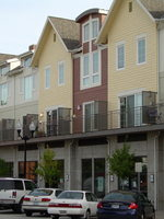 a photo of rows of townhomes above businesses and parking