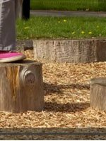 children's feet playing on wooden stumps in play area