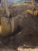 gold shovels in dirt during a groundbreaking ceremony