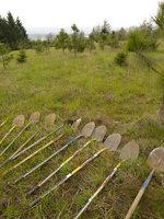 Shovels lined up on a grassy hillside in preparation for maintenance work