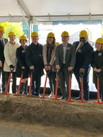 Elected officials pose for a portrait with shovels and hard hats during a groundbreaking ceremony.