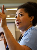 a woman raises her hand while addressing her group