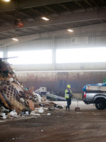 transfer station staff person in a yellow vest stands near big pile of garbage