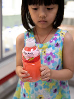 a young girl holds a plastic juice bottle