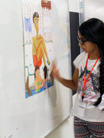 a little girl stands in front of a painting in her school hallway