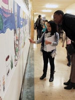 a little girl and a woman look at art work together in a school hallway