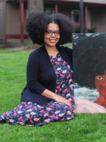 an artist sits on a grassy lawn while holding a painting she created
