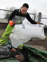 A man empties a large white trash bag onto the ground to sort through its contents