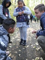 naturalist talking to students about woolly bear caterpillar on ground