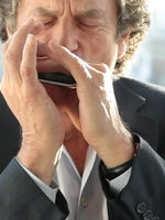 A man riffing on a harmonica