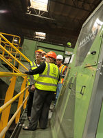 Metro counselors in hard hats check out a recycling conveyor belt that uses robotic arms to sort materials