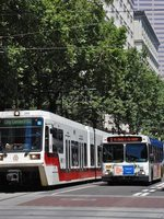 MAX train and bus side by side on Portland Mall, 5th and Yamhill