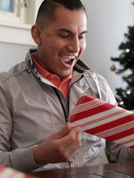 A man reacts with excitement to a festively wrapped holiday present