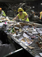 workers at a materials sorting facility pull out items that don't belong there