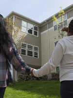 woman and daughter holding hands and looking at an apartment building