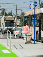 People board and disembark from a TriMet bus on NE Halsey Street.