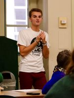 a high school student speaks to peers at a meeting while standing