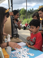 Metro staff explain cleaning products and provide information to a family at a healthy homes booth