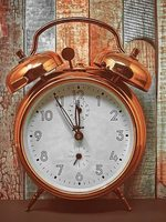 antique copper alarm clock displaying a time of 11:55