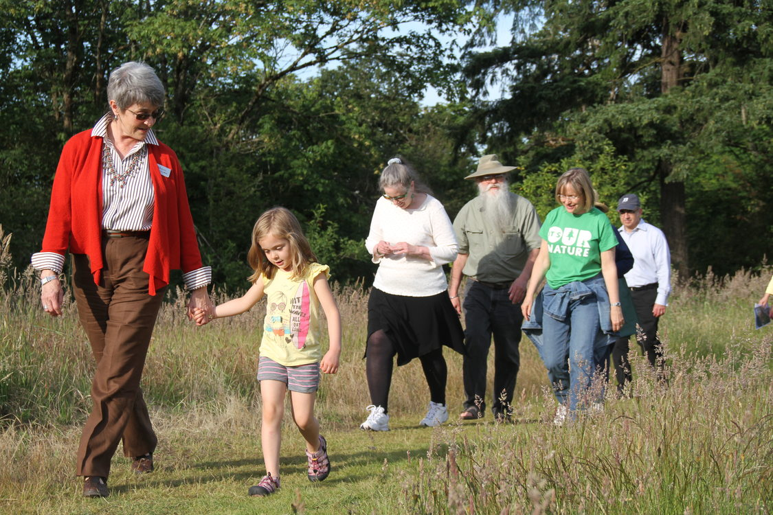 a photo of people walking along a trail in a prairie field