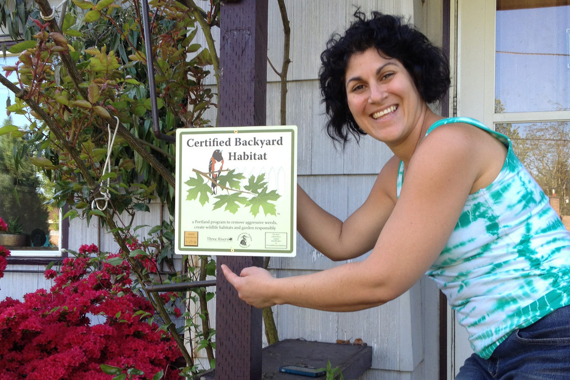 photo of woman with backyard habitat sign