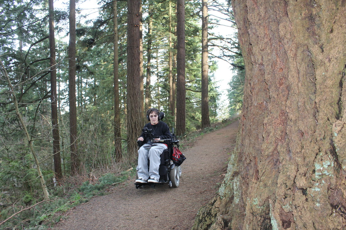 photo of Georgena Moran capturing video as she moves along a trail in her wheelchair