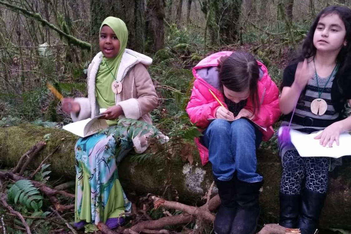 young girls writing in notebooks while sitting on a moss-covered log