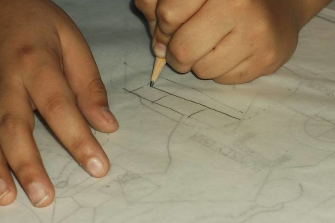 person using tracing paper and pencil to sketch designs for a park play area