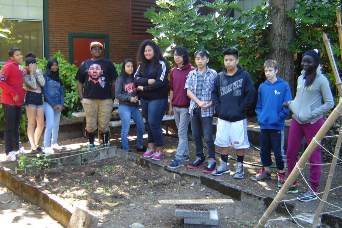 students at George Middle School standing next to their community garden