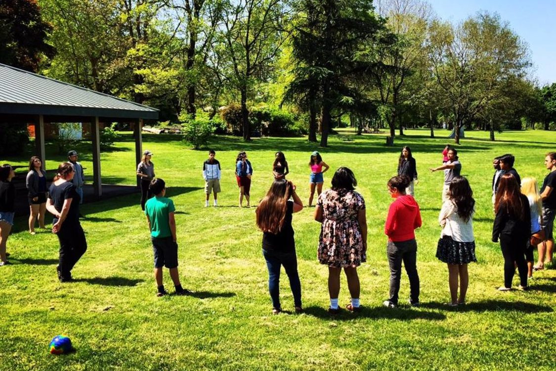 kids from Momentum Alliance standing in a circle on the grass of a park
