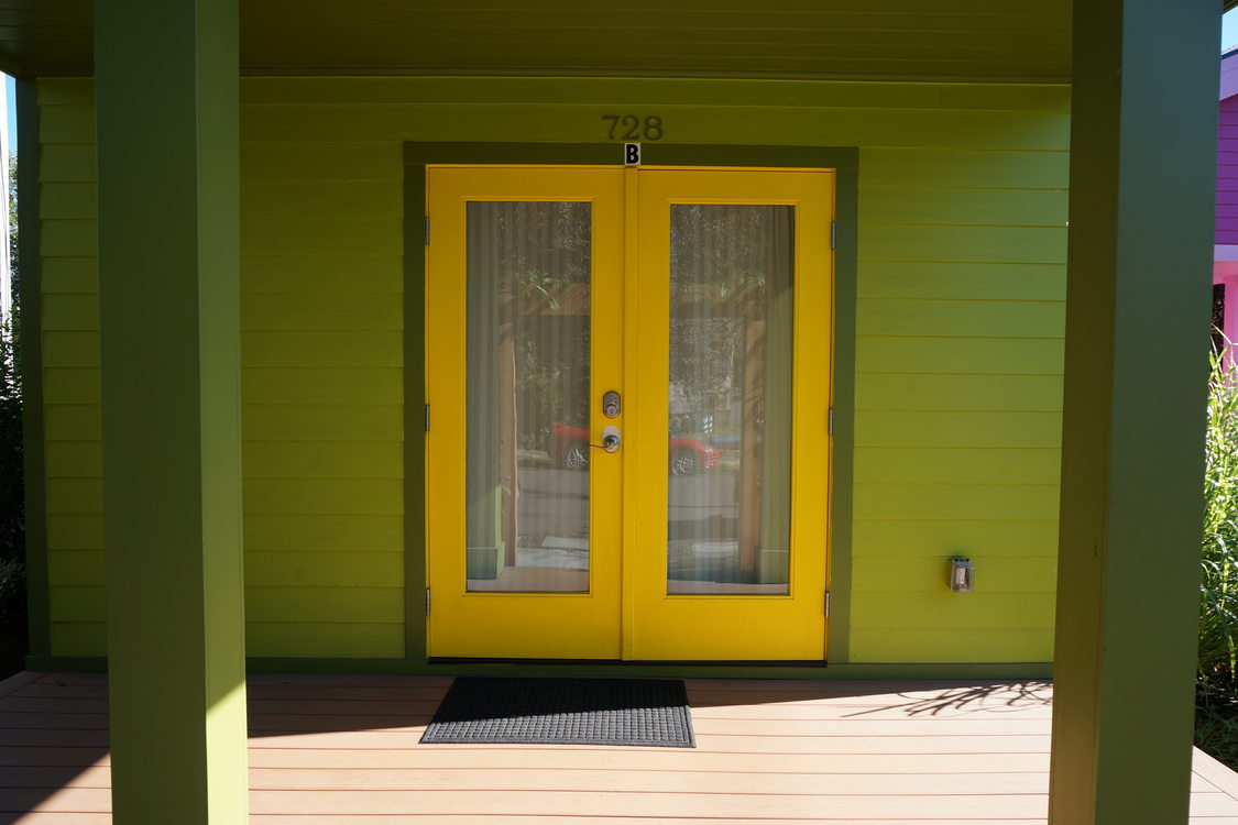 Green house with double yellow front doors