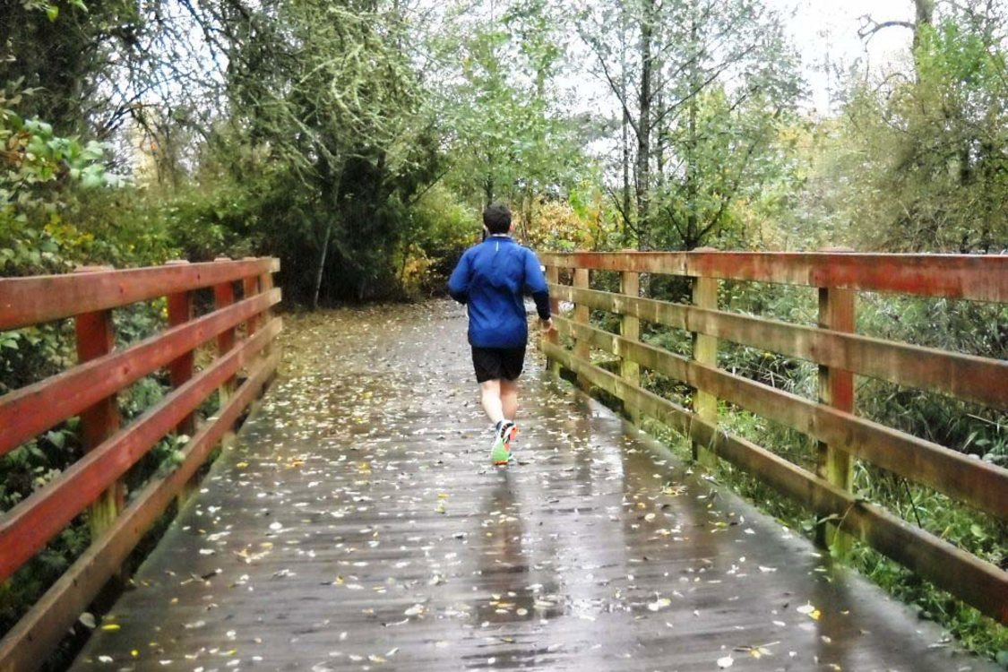 photo of jogger on tributary bridge