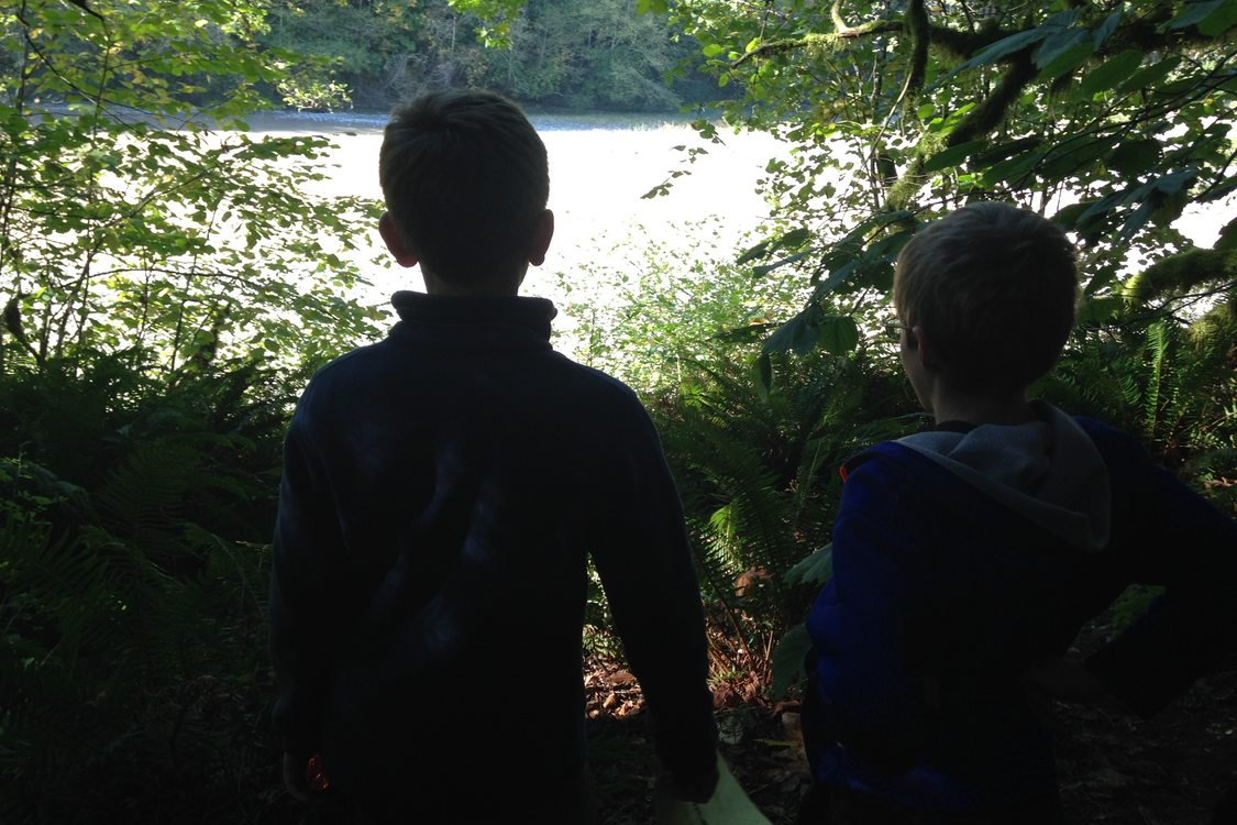 two children looking through trees at a river in the distance