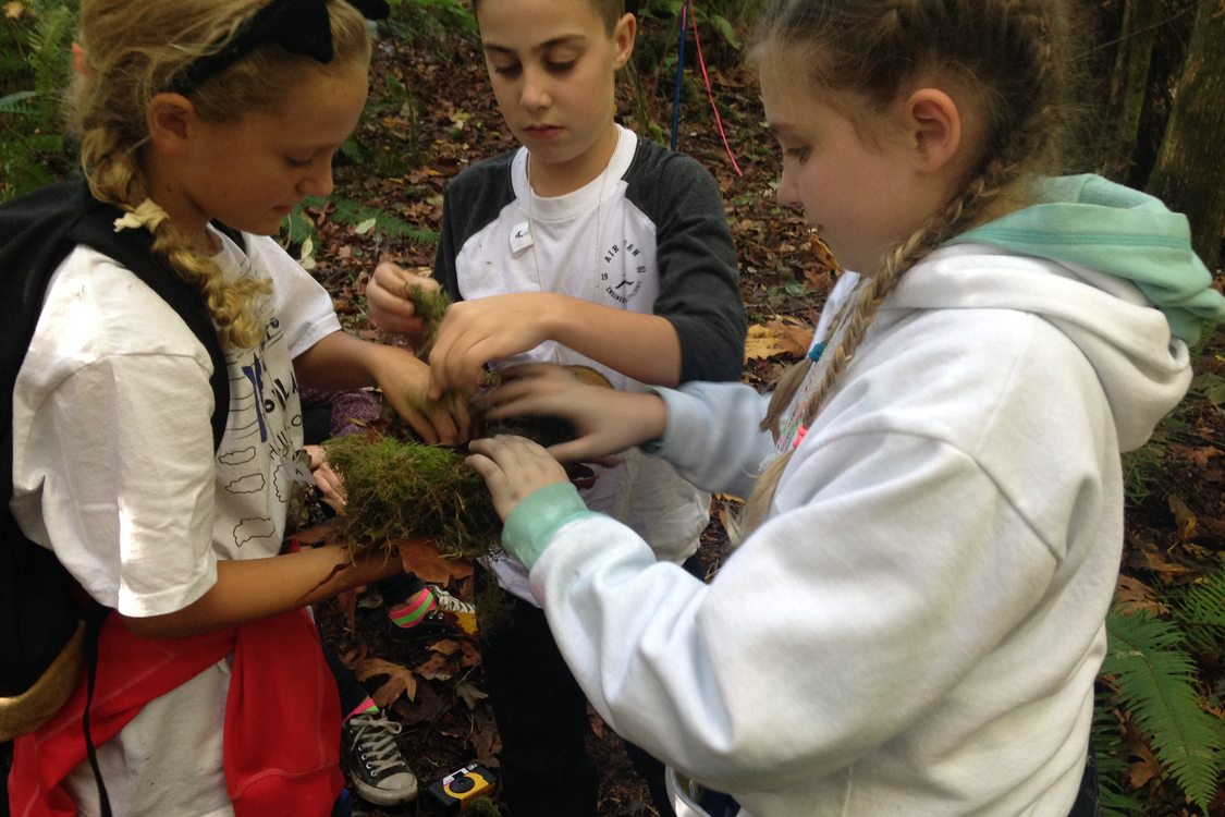 three children learning to build bird nests at Outdoor School