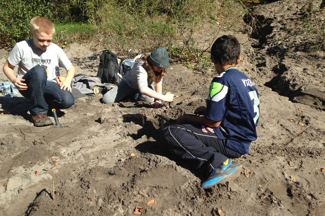 Outdoor School students digging in the sand on the banks of the Sandy River.