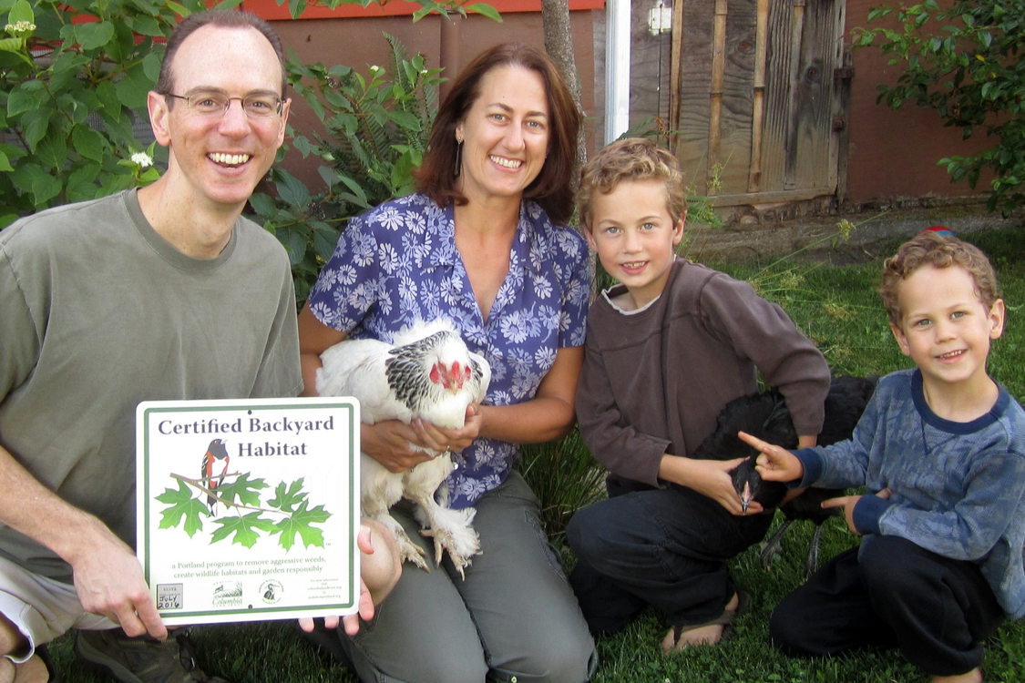 photo of a man holding a Certified Backyard Habitat sign, a woman holding a rooster and two boys holding a chicken