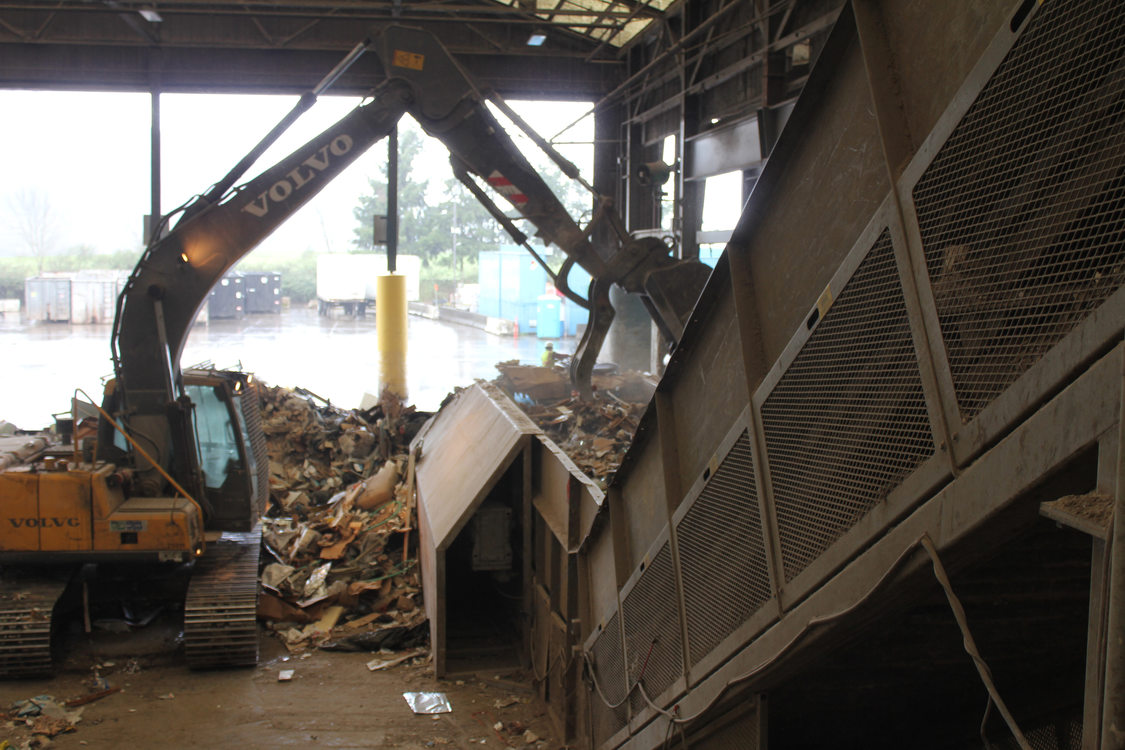 Dry waste from Bay 1 is dropped onto a ramping conveyor belt, to lift to workers who will pull out anything that can be recycled.