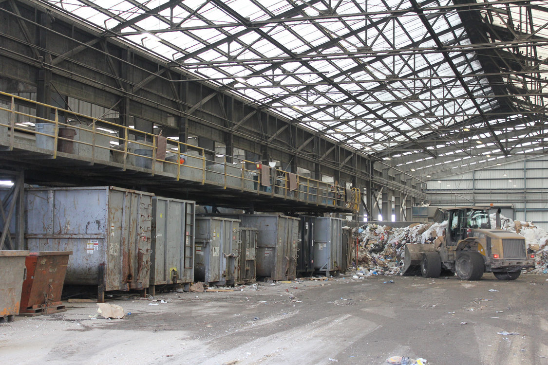 Another view of the sorting line. As workers pull recyclables, they drop them into designated bins below.
