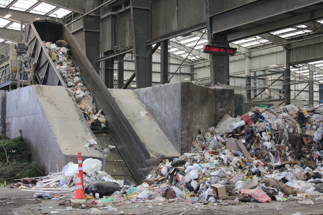 Non-salvageable waste is worked into a pit and up a ramp, where it will be compacted into a semi-truck trailer.