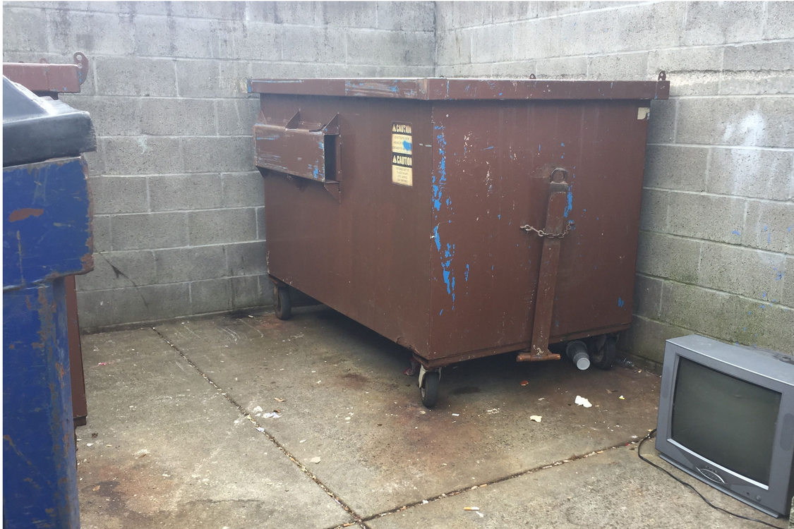 television next to dumpster