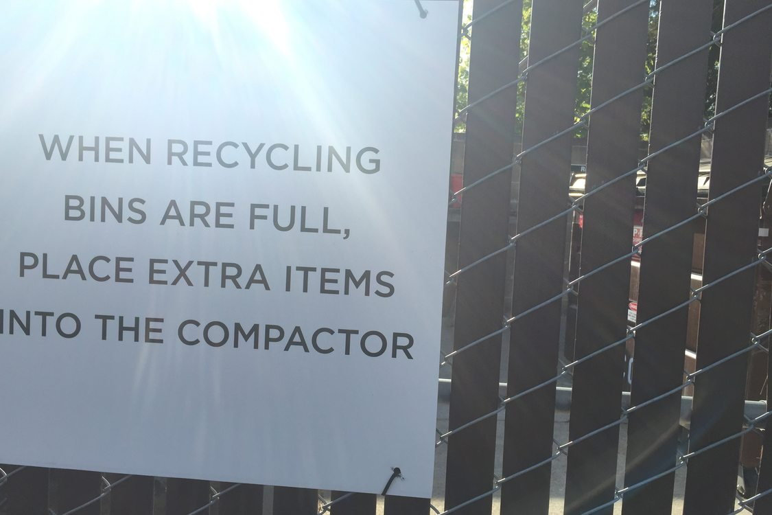 signs next to recycling bins with directions